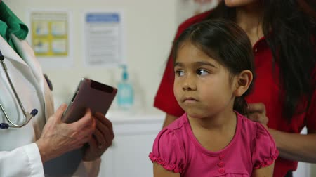 açıklayan : A cute little Hispanic girl listens to a doctor with an electronic tablet explain diagnosis and treatment to her mother.