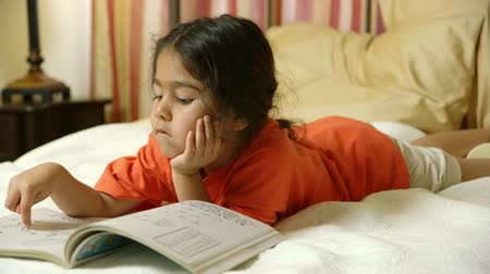 klidný : Lying on a bed, a cute little girl of Hispanic heritage coloring quietly in her coloring book looks up and smiles