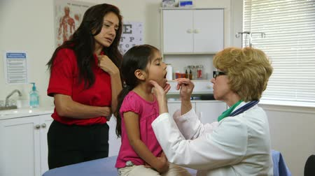 zkontrolovat : A Caucasian physician checks the throat of a cute little Hispanic girl while her mother looks on with concerned interest.