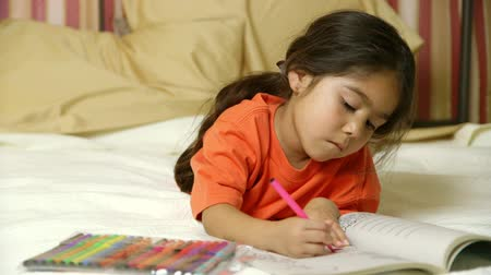 suçsuzluk : Lying on a bed, a cute little girl of Hispanic heritage colors quietly in her coloring book.