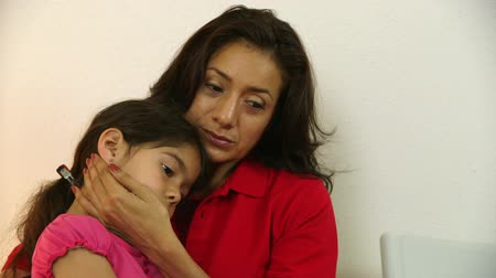 filha : A worried Hispanic single mom with little daughter waits in clinic waiting room for doctor to see her sick child.