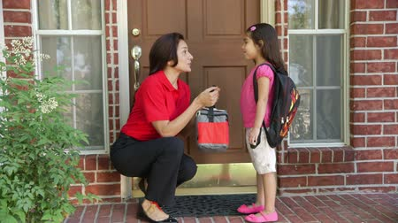 мама : A little Hispanic girl wearing a backpack gives her mother a little kiss after getting her lunch bag and a cheerful send off to school. Стоковые видеозаписи