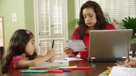 filha : A single mom worries about how to pay bills while children color peacefully unaware of the stress she is feeling.