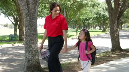 batoh : A cheerful single mom walks her cute little girl home after school on beautiful afternoon.