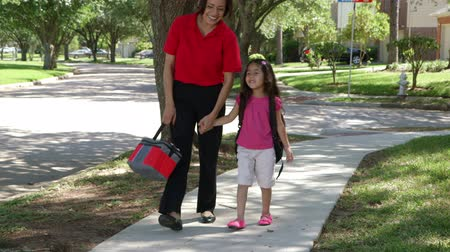 filha : A cheerful single Hispanic mom walks with her cute little girl after school on beautiful afternoon. Vídeos