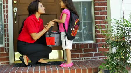 filha : A little Hispanic girl wearing a backpack gives her mother a little kiss after getting her lunch bag and a cheerful send off to school. slow motion.