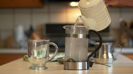 devise : In a domestic kitchen a man adds water to a French Coffee Press. Slow motion footage. Stock Footage