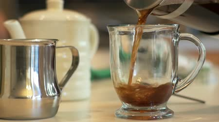 ceramika : Slow motion footage of coffee being poured into a glass mug.