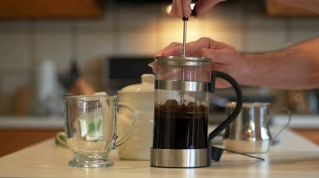 devise : In a domestic kitchen a man uses a French coffee press to make his morning java. Slow motion footage. Stock Footage