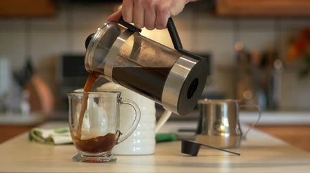 devise : In a domestic kitchen a man pours java he has made with a French coffee press into a transparent glass mug. Slow motion