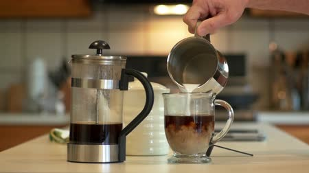 kufel : In a domestic kitchen a man adds milk to the coffee he has made with a French Coffee Press. Slow motion footage.