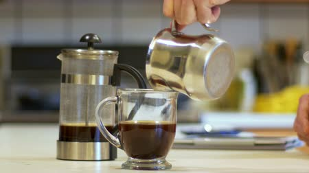 devise : A man adding milk to his coffee that he has used a coffee press to make.