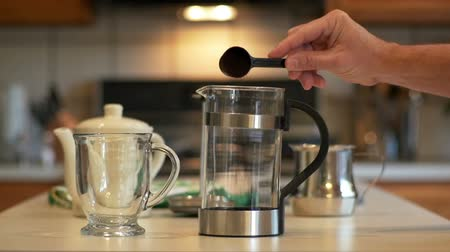 devise : In a domestic kitchen a man adds ground coffee to a French Coffee Press. Slow motion footage.