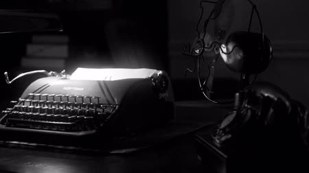 сбор винограда : Great establishing shot for classic film Noir of a desk with an old manual typewriter and vintage electric fan in dimly lit room. Стоковые видеозаписи