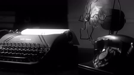 período : Radial dolly move of a desk with an old manual typewriter and vintage electric fan in dimly lit room. film Noir at 4k