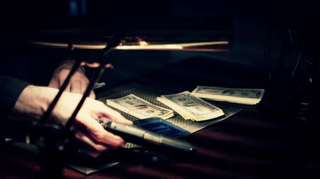 boss : Gangster in a dimly lit room counting money and picking up his pistol
