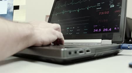 vital signs : A technician or doctor reviewing vital signs on a laptop in the monitoring station of a medical clinic.
