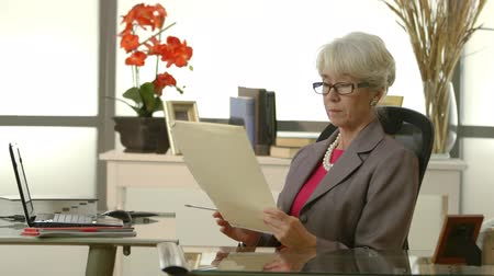 deneyimli : An older female CEO or senior executive in her office starts to work but is interrupted by a telephone call.
