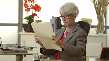 ügy : An older female CEO or lawyer in office looking over a legal document appears distracted or preoccupied. Stock mozgókép