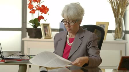 főnök : An older female CEO working in her office looks over then lowers her reading glasses and smiles Stock mozgókép