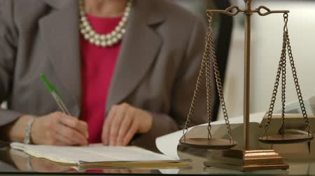 advokát : Focus is on the scales of justice with a female attorney out of focus working in the background.