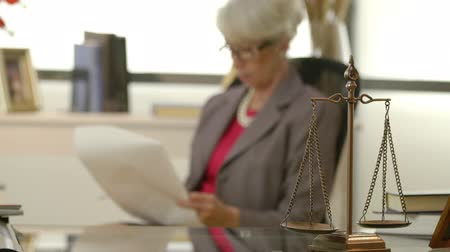 trabalhar fora : Focus is on the scales of justice with a mature female attorney out of focus working in the background.