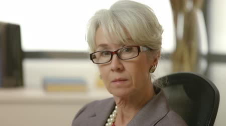 advokát : An older female CEO or senior executive turns slowly and looks intently into the camera.