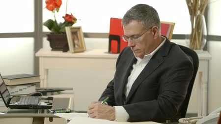владелец : A mature CEO in his office stops working then removes reading glasses and smiles