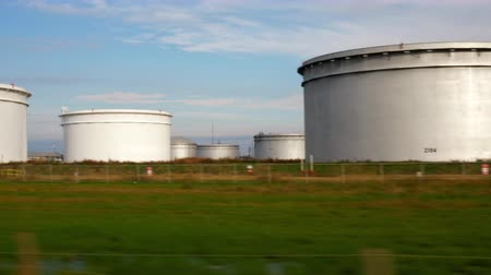 pracodawca : Driving along road next to a storage tanks standard to the petrochemical industry.