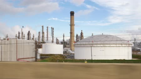 farpado : Slow motion driving past a large oil refinery or petrochemical processing plant.