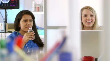colega de trabalho : Two pretty nurses or medical interns smiling as they engage in lively conversation with someone off scene. Stock Footage