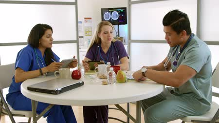 descanso : A young Asian intern walks into hospital break room and discusses issue with his fellow interns. Stock Footage