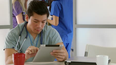 egészségügy és az orvostudomány : Scene tracks around to reveal a young Asian intern sitting in hospital lounge or break room uses an electronic tablet pc with medical staff working in background.
