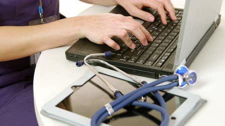医疗保健 : Close up of the hands of a young female nurse or doctor typing on a laptop with a tablet pc and stethoscope nearby 影像素材