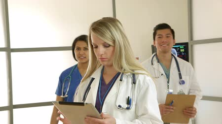 egészségügy és az orvostudomány : A young female medical intern or doctor reviewing data on a tablet is joined by the members of the team.
