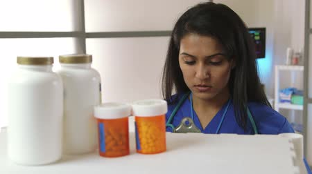 verifying : A pretty medical assistant or nurse takes inventory of medications in stock. Stock Footage