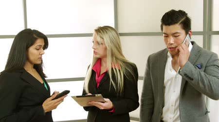 относящийся к разным культурам : Business associates in a building foyer or lobby using electronic communication devices consult with one another.