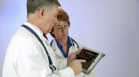 vital signs : Two mature doctors monitor remotely the vital signs and EKG of a patient using a digital tablet pc.