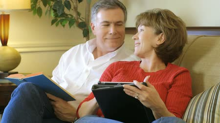 wife : A mature couple sitting on a couch together one reading a book and the other using an electronic tablet pc.
