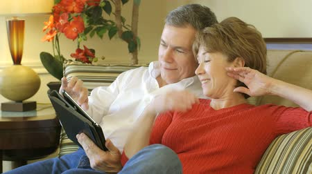 casal heterossexual : A mature couple sitting on a couch together enjoying what they see on their electronic tablet pc.