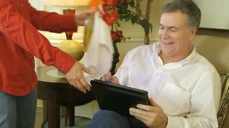 sıkıcı iş : A man enjoying what he is engaged in on his electronic tablet is interrupted by his wife who changes his mood by handing him cleaning materials.