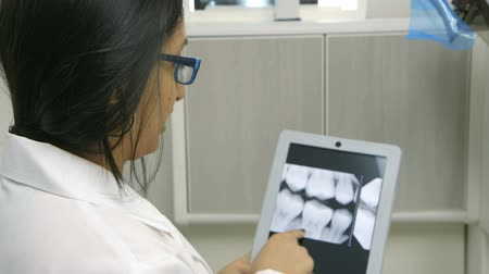интерн : A female dentist or intern reviewing a dental x-ray explains what she sees to a patient who is off camera.