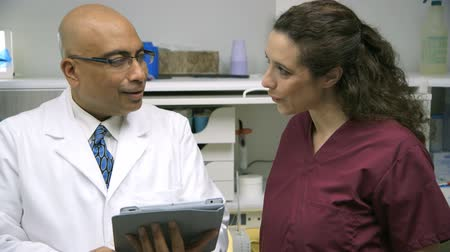 hallgat : A male dentist reviewing some data he has on an electronic tablet gives instructions to his dental assistant.