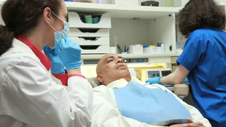 интерн : A female dentist receives a dental implement from her young intern assistant prior to commencing to examine the male patient in the exam chair.