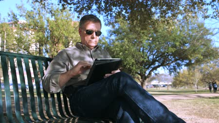 repousante : A handsome mature man relaxing on a park bench shaded by a large tree uses his electronic tablet pc. Stock Footage