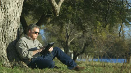 repousante : Polarized sunglasses are helpful to this man sitting by a large tree using an electronic tablet pc in bright sunlight.