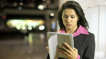 asian and indian ethnicities : A pretty brunette businesswoman absorbed by what she reads on her electronic tablet stops suddenly and stares with intensity into the camera.