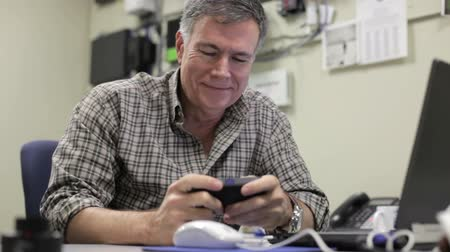 administrador : An IT administrator in his office chuckles upon reading a humorous text message.