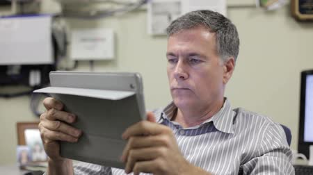 deneyimli : A man in his rather industrial looking office using a digital tablet pc. Stok Video