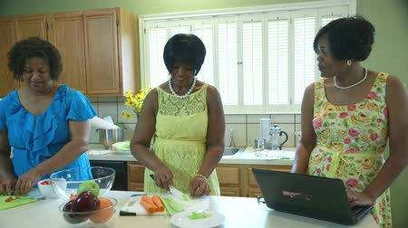 africký : Three lovely African American ladies in a kitchen preparing lunch with one using a laptop. Dostupné videozáznamy